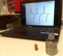 Foreground: pressure cell and sample of vulcanized natural rubber subjected to several cycles of compression and decompression. Background: chart showing temperature measurements as a function of time for different pressure variations.